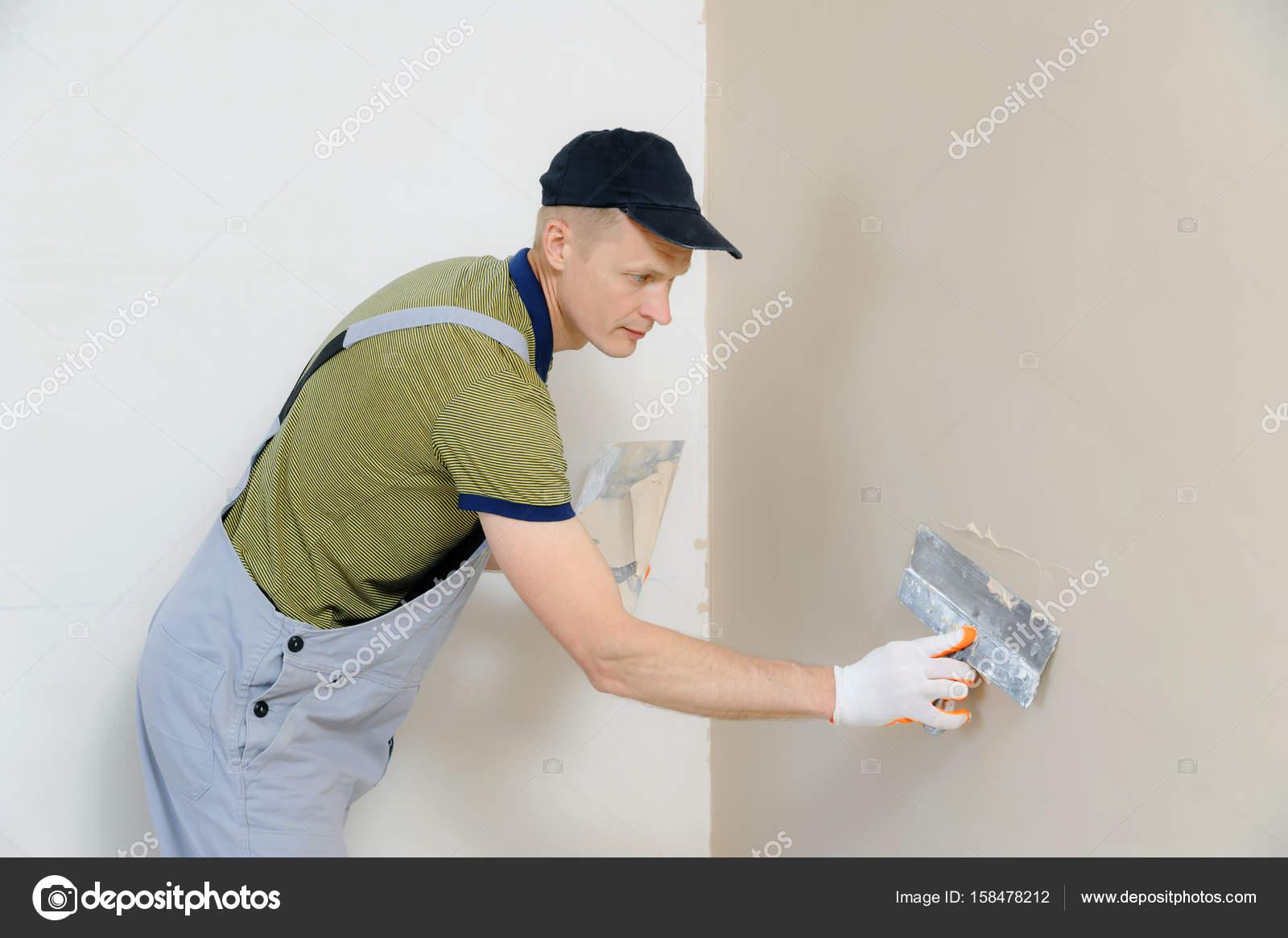 Un lavoratore intonacare una parete foto stock with come - Intonacare muro esterno ...