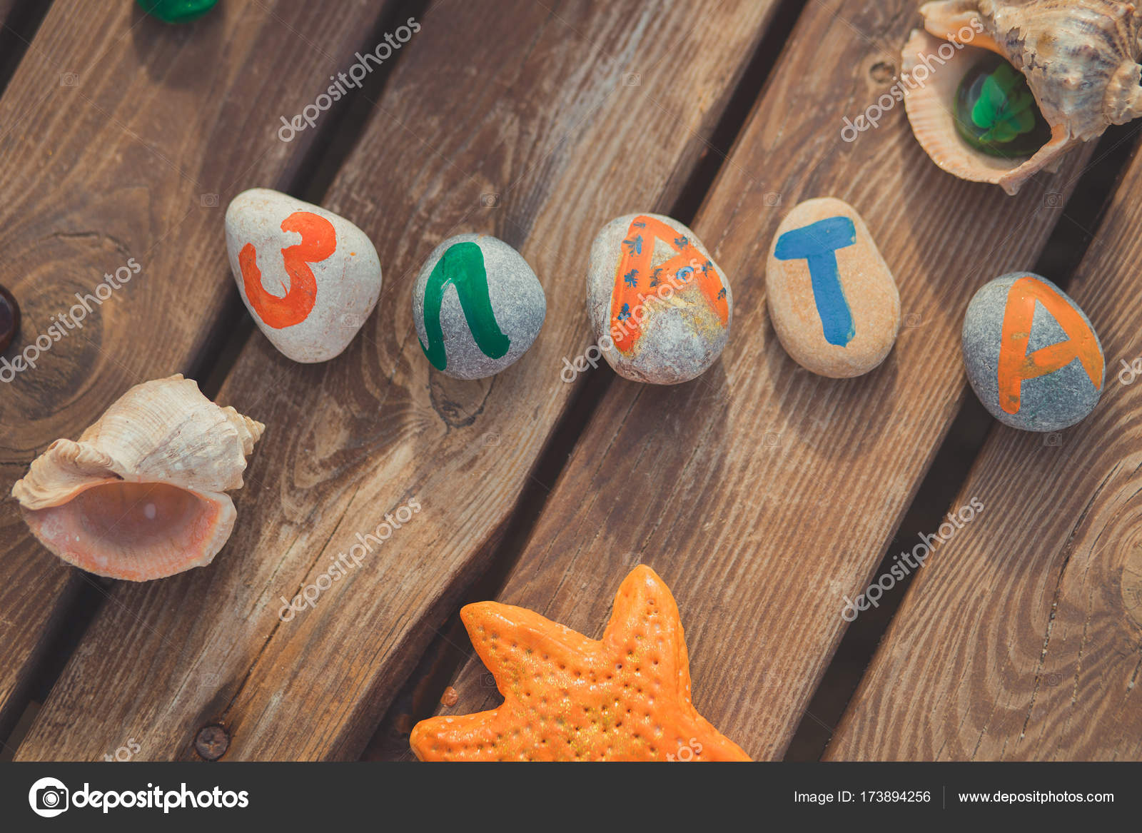 a31743390 Beach stones with colourful letters on wooden table close to sea shell —  Stock Photo