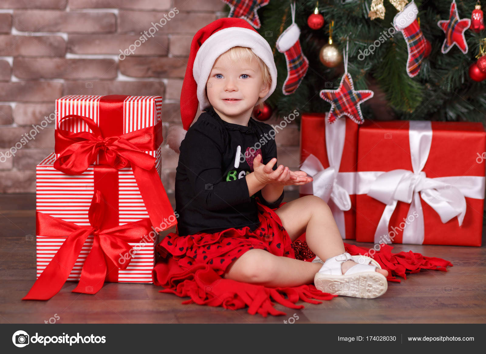 29ae6496eb2b3 Christmas beautiful cute baby girl posing in casual clothes close to new  year pine green tree with presents pillows and toy horse in studio scene–  stock ...