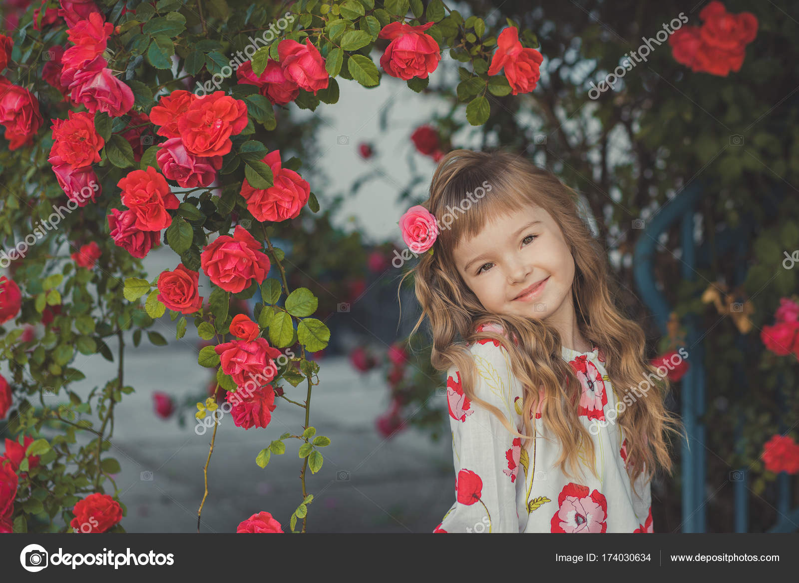 cute baby girl with blond curly hairs and happy bright child eyes