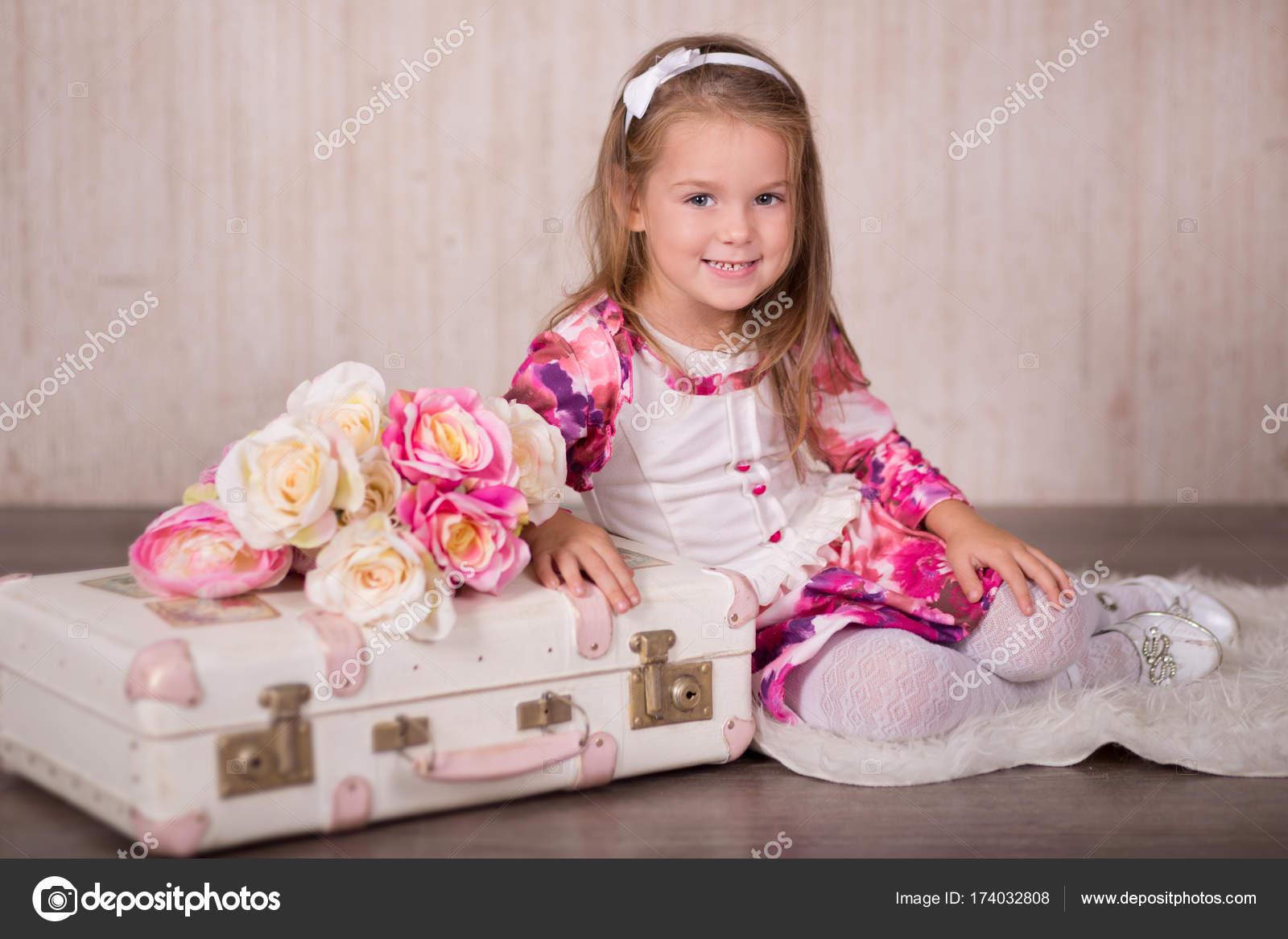 Linda niña con pelos morenas rosa las mejillas y ojos verdes posando ...