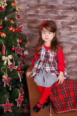 Young brunette dolly lady girl stylish dressed in red dress costume chequers check tartan skirt strap shoes smiling posing sitting in studio christmas tree with pout lips and pink cheeks.