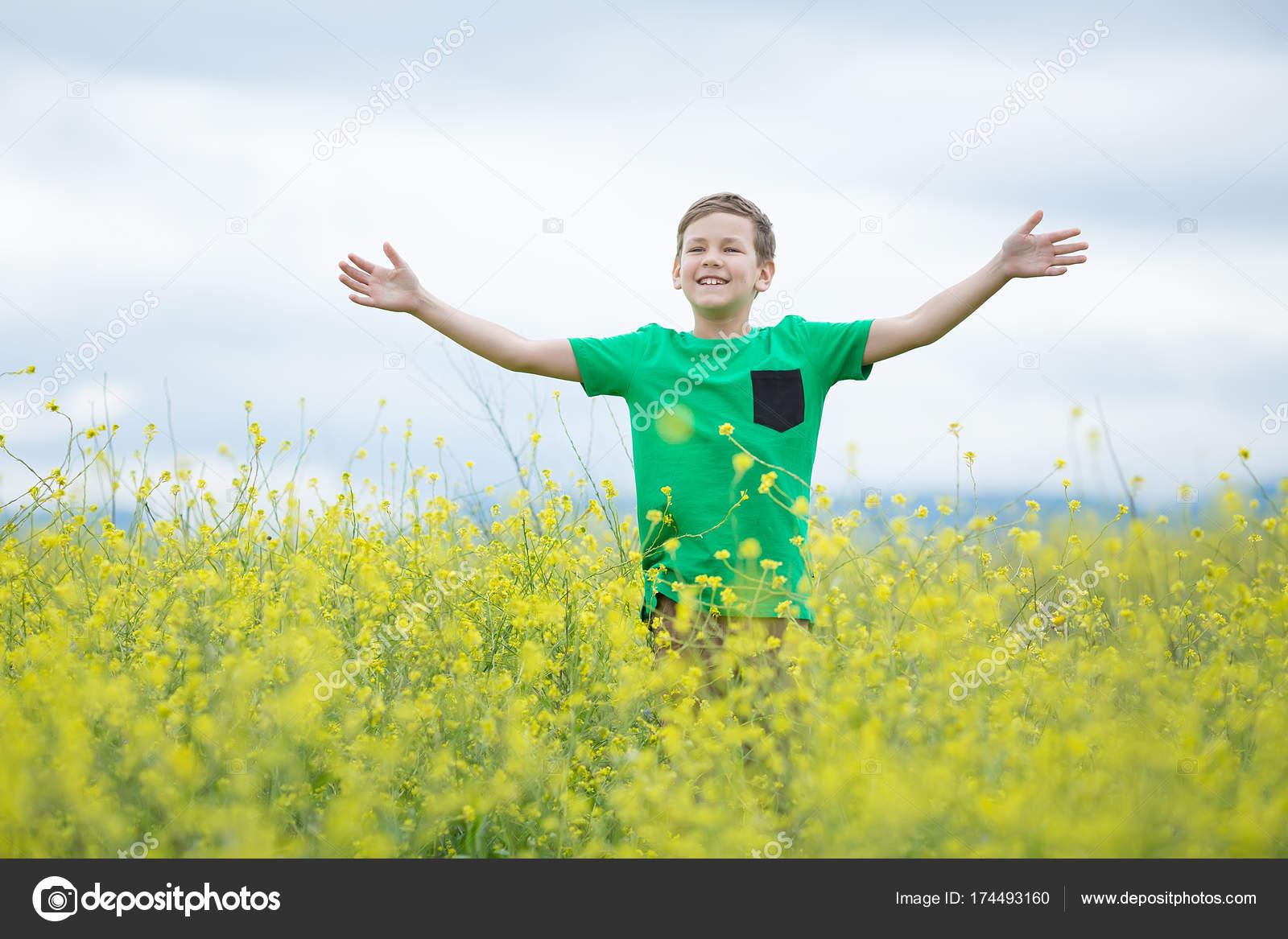 Felice bello ragazzino ragazzino sveglio su fiori di tarassaco erba ...