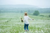 Fotografie beautiful blond girl lady woman on green field with flowers chamomile wearing jeans hat white shirt under rain in may spring. Rural scene