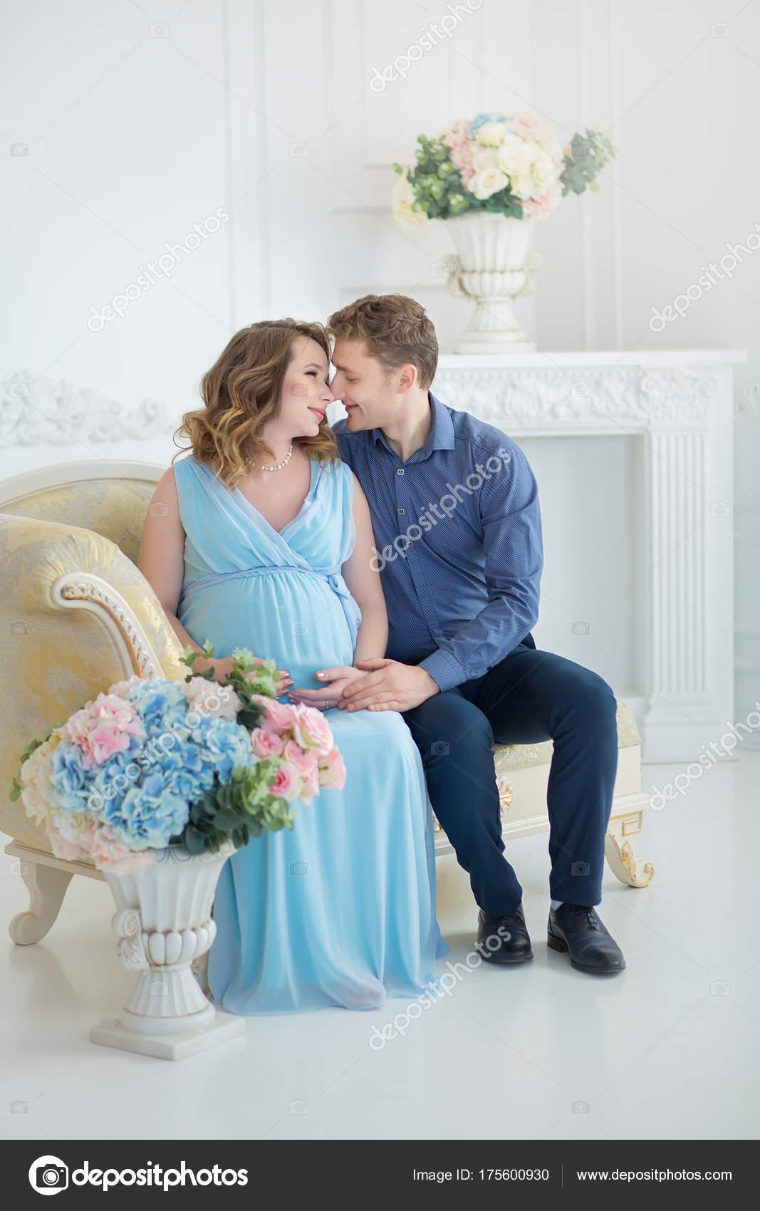 スタジオ ポートレート、屋内でやがて生まれる子供かわいい赤赤ちゃん靴を見て幸せな親になるカップル\u2013 ストック画像