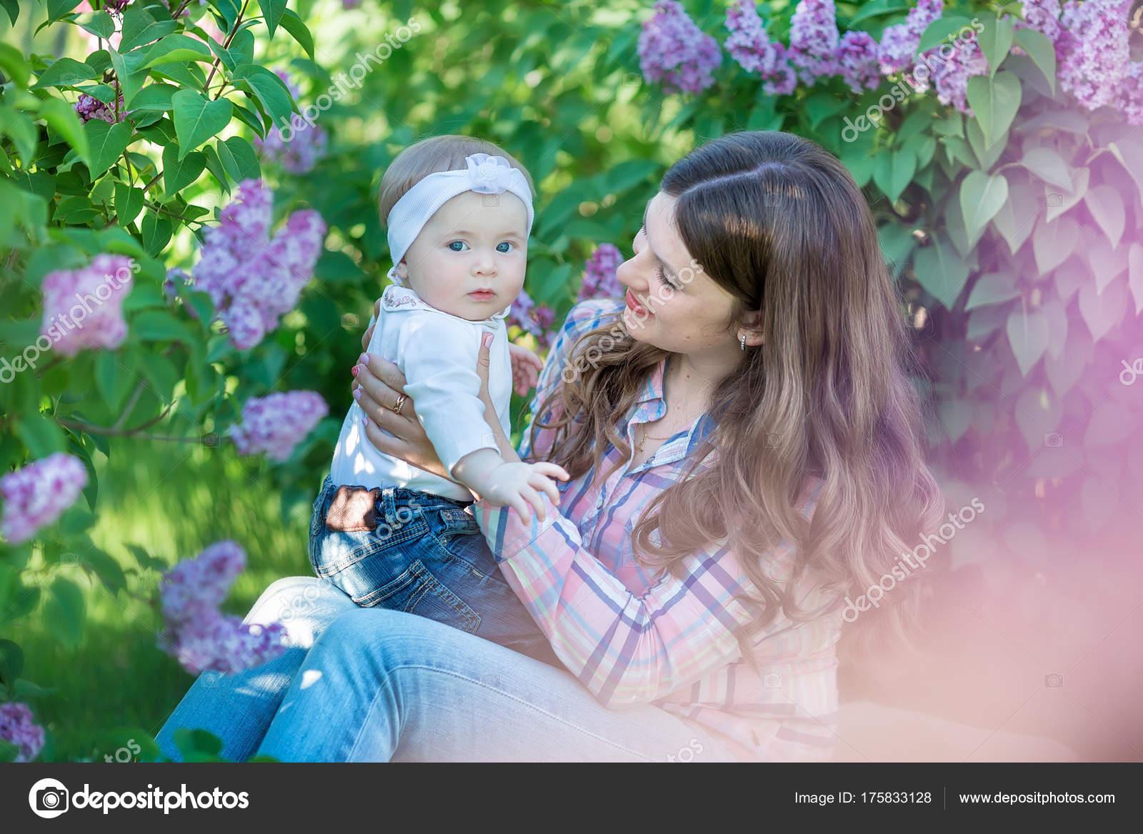 Feliz madre e hija con manzanas verdes en el jardín de flores lilas — Fotos  de