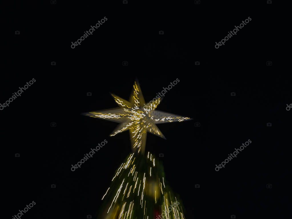 zoom burst  light of artificial pine christmas tree with star on top , bokeh of LED decorative light defocused background and textured,  for Christmas Eve , New Year party holiday and celebration