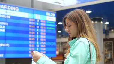 Young Woman Looks At The Information Board Of Departures At The Airport.