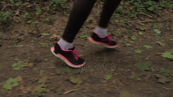 Nahaufnahme athletischer weiblicher Beine beim Laufen an der Forststraße