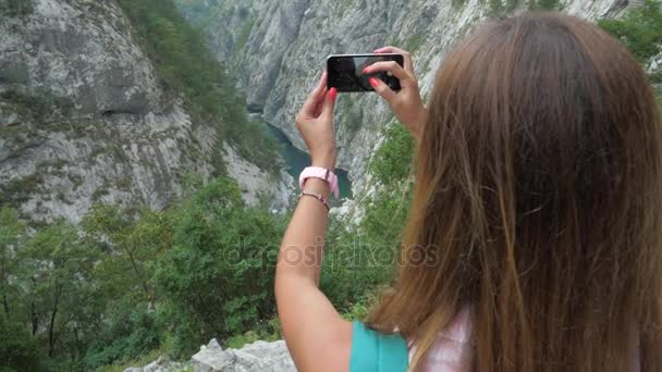 Reisende fotografiert malerische Bergschlucht mit dem Smartphone