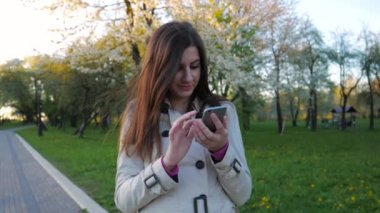 Lovely and beautiful brunette girl in coat uses the phone standing in a Park