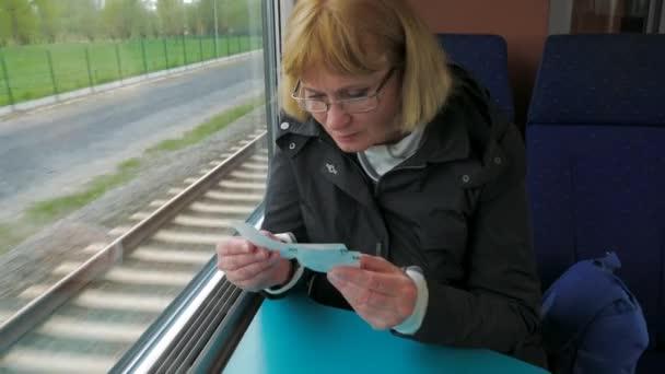 Eine Frau fährt den Hochgeschwindigkeitszug am Fenster sitzen und prüft die tickets