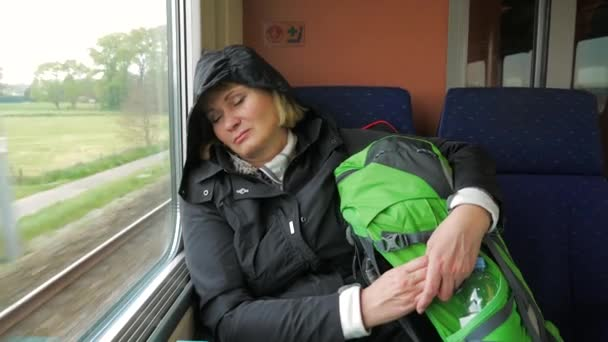 Tired woman rides on the train and sleeps against the window.