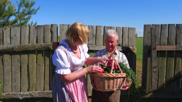 Old man holding a basket of ripe vegetables collected,and a woman examines them.