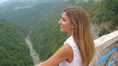 Young Woman Looking At The Mountains Standing On A Bridge Over A Deep Canyon
