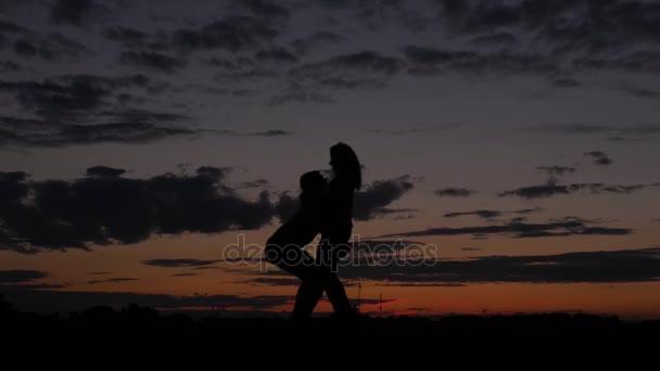 Silueta romantický pár líbání při západu slunce, muž zvedne a zapne A žena