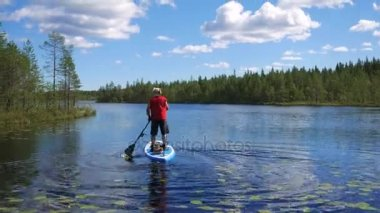 Man Floats On Lake On A Inflatable Boat Standing On Her, Rowing With Hands Oars