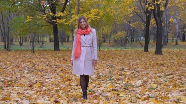 Dáma v béžový kabát a oranžový šátek na podzim koberec žluté listy
