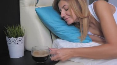 Woman Wakes Up In Bed Reaching For Cup Of Coffee On Nightstand And Drinks