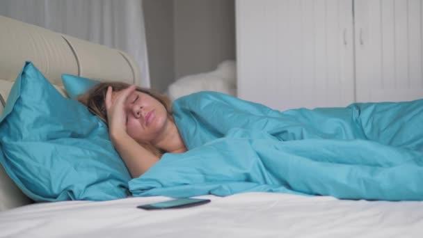 Valóban alszik nő felébred, és nézi a telefon dob és elalszik