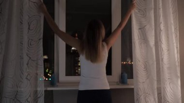 Woman Stands At The Windows At Night Looking At Street Lights, Curtains