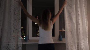Een jonge vrouw ziet er bang achter de gordijnen in het venster, ze ...
