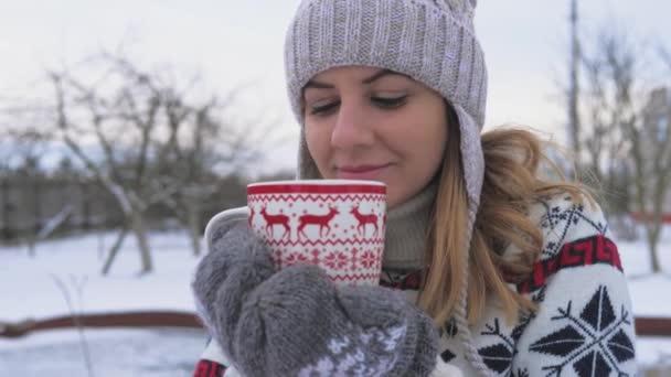 Frau in warmer Kleidung trinkt heißen Tee oder Kaffee aus Tasse am Wintermorgen 4k