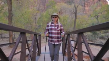 Active Woman Hiking Goes Through a River Bridge In Zion Park USA, Slow Motion 4K