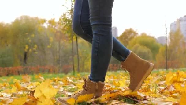 Closeup žena nohy v botách procházky v parku s žluté listí