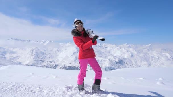 Žena držící lyže na ramena, stojící proti pozadí hory