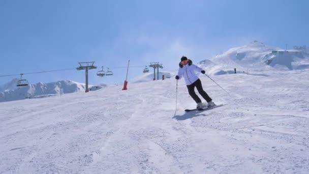 in Bewegung eine Skirennläuferin beim Carven die Skipiste des Berges hinunter