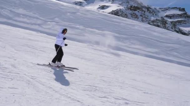 in Bewegungs-Seitenansicht, Skifahrerin fährt auf Skiern den Hang des Berges hinunter