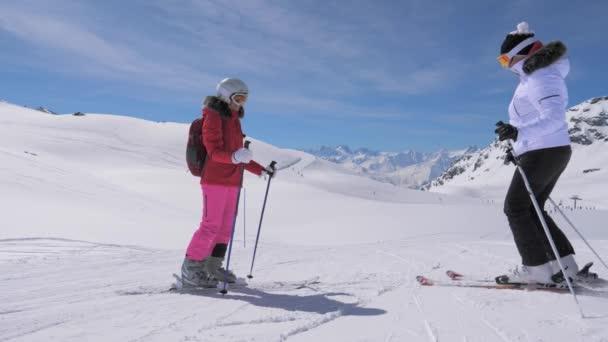 Skifahrerin steht an einem Berghang, ihr Freund rollt zu ihr hinunter und gibt ihr fünf