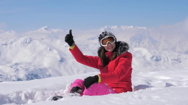 Lyžař žena ukazuje ruka Ok a prst se na pozadí zasněžené hory