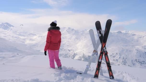 Skirennläuferin steht oben auf dem Berg und schaut weg