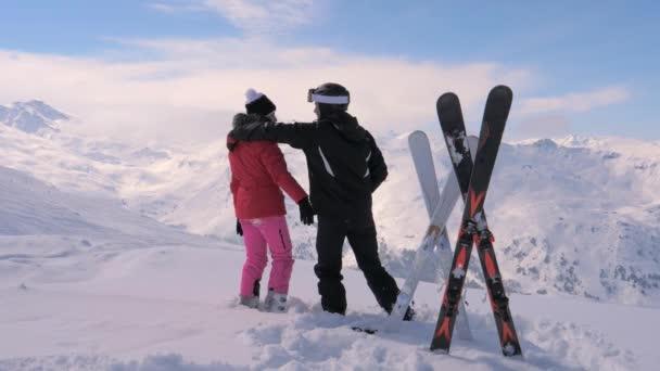 Verliebte Skifahrer küssen sich und umarmen sich auf dem Gipfel des Berges