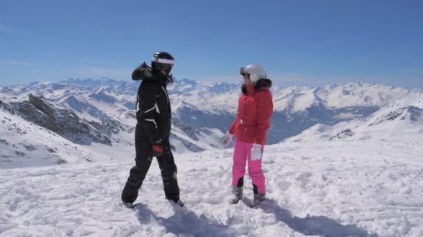 glückliches Paar von Skifahrern, die oben auf dem Berg stehen und zurückblicken
