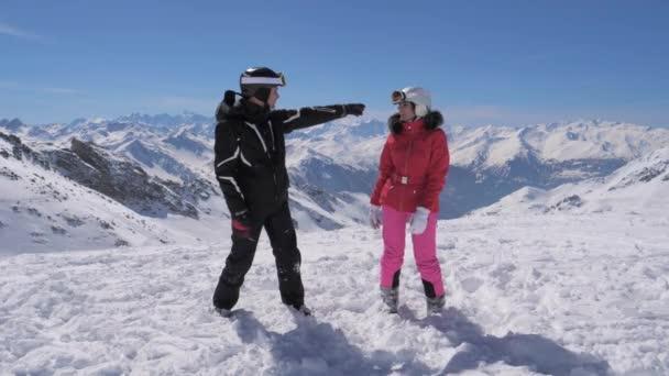 Skifahrer sahen im Gebirgstal etwas Interessantes und zeigten sich gegenseitig die Hand