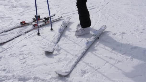 ein Skifahrer schnallt seinen Abfahrtsski auf weißen Skischuhen an