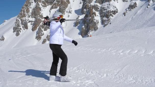 Lyžař jít vpřed s sjezdové lyže na rameni Ner