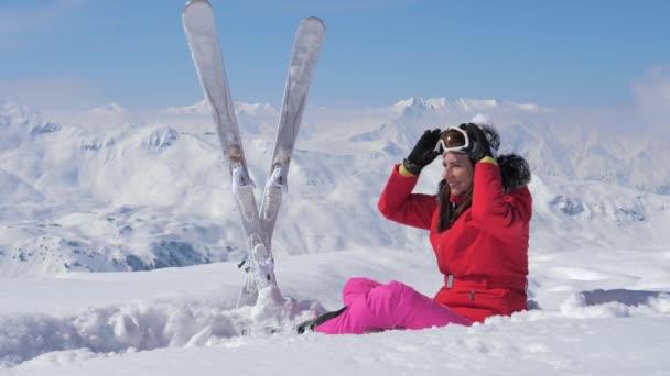 eine schöne Skifahrerin sitzt im Schnee und setzt ihre Skibrille auf