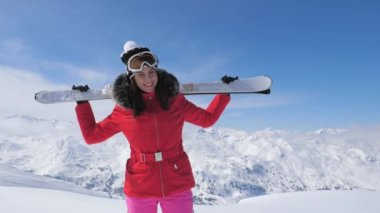 Smiling Pretty Woman Skier Stands On A Hillside, Holding Skis On Her Shoulders