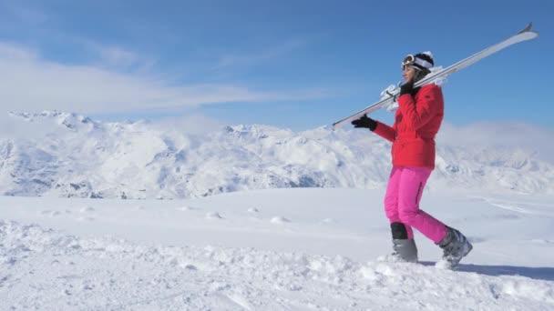 in Bewegung eine Skifahrerin auf den Hangberg, Ski auf der Schulter