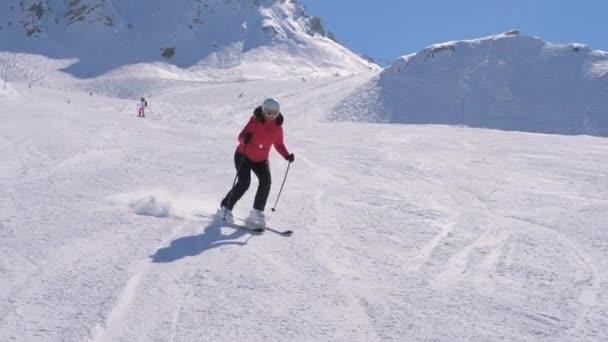 Sportliche Skirennläuferinnen carven im Winterskigebiet die Piste hinunter