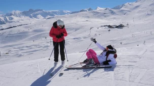 Žena lyžař pomáhá další vzestup na nohy po pádu na sjezdovce