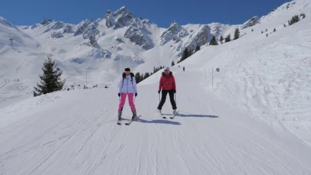 Porträt zweier Skifahrerinnen, die im Winter den idealen Hang des Berges hinunterfahren