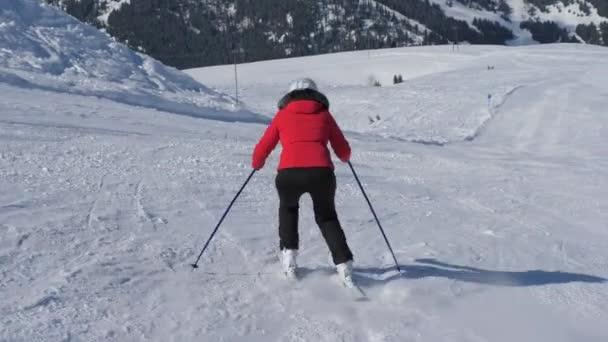 Zralá žena lyžař řezbářské svahu v lyžařském středisku hory v zimě