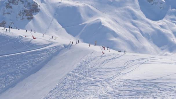 sonniger Tag in den schneebedeckten Bergen eines Skigebietes, viele Skifahrer auf der Piste
