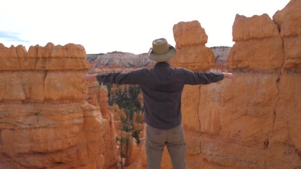 A Man Admires The Nature Of The Bryce Canyon, Raises His Hand And Turns Aside