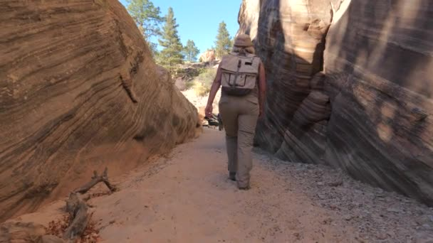 Hiker zralá žena chodí mezi hladké a vlnité skály kaňonu